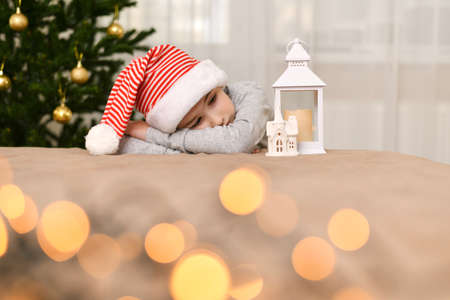 Sad kid in a striped cap lies at the Christmas tree and looks at the house lantern. Stock fotó