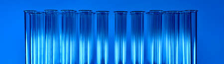 Blue banner with glowing bright glass test tubes, in several rows. Fragment of the top with necks. They shimmer with shades of monochrome. The first stage of vaccination.