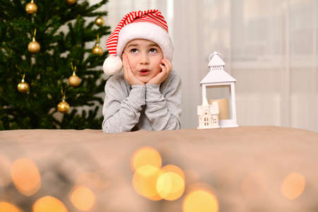 A child in a carnival striped cap rolled his eyes in surprise and clasped his face with his hands. Sitting by the Christmas tree. Stock fotó