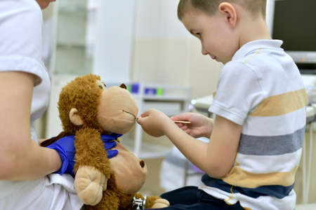 The child at the reception at the clinic examines the mouth cavity with a medical spatula of a toy plush monkey, which is in the hands of the doctor's blue protective gloves.