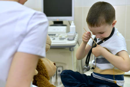 The doctor and the patient, a boy, with his head bowed to his pocket, inserts a medical spatula, with a stethoscope hanging around his neck. In the clinic for consultation. Standard-Bild