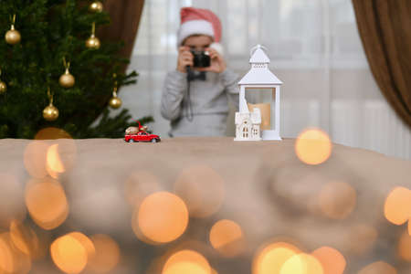 A car with a bag of gifts drives up to the house of the lantern. The child, on a distant blurred background, in the cap of the dwarf at the Christmas tree takes pictures.