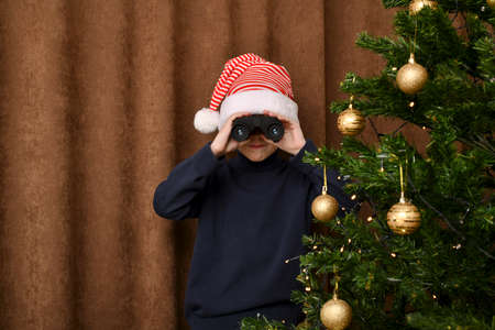 A boy with compressed lips, impatiently, in a striped cap, looks out through the binoculars of Santa Claus with gifts, a guard near the Christmas tree. On a brown curtain background. Stock fotó