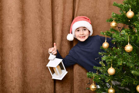 The boy in Santa cap, delighted and pleasantly surprised, half behind the Christmas tree, with a portable lantern house. Stock fotó