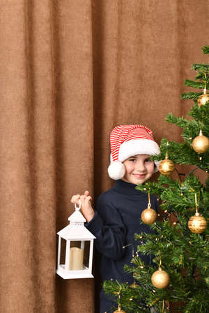 A child with a lantern in his hand stands embarrassedly smiling near a dressed Christmas tree in a carnival red white Santa cap.
