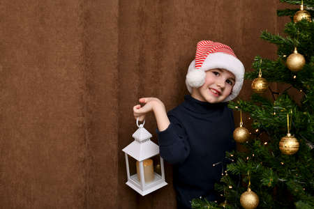The child cheerfully imagines with a lantern in his hand near the Christmas tree.
