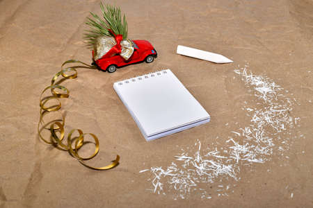 New Year composition from a red car with a bag of gifts, rides around a white notebook and a pencil with white shavings.