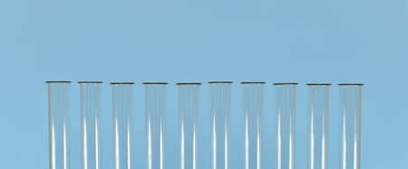 The necks of empty glass test tubes, lined up on a blue background, banner. They're not filled with anything. Stock fotó