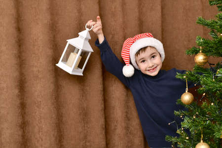 Smiling kid, with an enthusiastic face, in a striped Santa Claus cap, suddenly looked out from behind the Christmas tree with a lantern, in a high pitched hand.