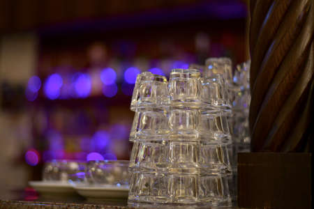 Small glass transparent cups with neat stack vertical rows on the bar. Amid the lights side of the showcase. Stock fotó