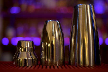 A set of three metallic stainless glossy shakers lined up in order of height. Against the background of purple lights, close-up from the front. Stock fotó