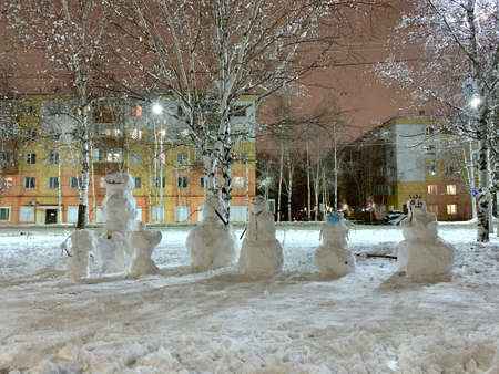 A company of a variety of snow-covered snowmen. On the street of the city in winter. Big and small, scary and funny, one in a medical protective mask. Stock fotó