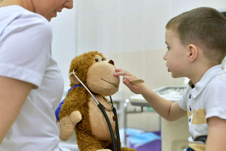 A child with knowledge of the matter examines the muzzle of a plush monkey. At a doctor appointment at the clinic. Stock fotó