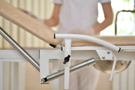 Fragment with the armrest of the gynecological chair on a blurred background medical worker in a white uniform. In the office of the clinic against the background of the window.