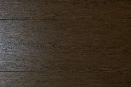 An example of the color and texture of the background of the wooden surface of a fragment of the door of a room in gray brown color. Divided into three horizontal boards. On the right it is lit.