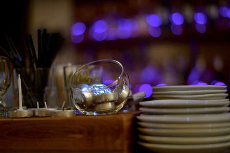 Plates and decorative items, candles, candlesticks, drinks tubes. On the bar against the background of lights purple side.