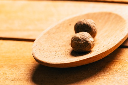 Nutmeg in a spoon on a wooden background. Stock Photo