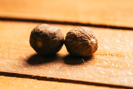 some nutmeg spice whole on a wooden background.