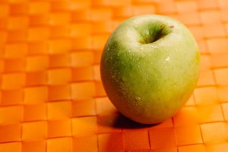 fresh green apple on a orange napkin.