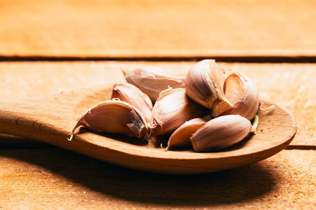 eating utensils: Garlic in a wooden spoon on a light background.