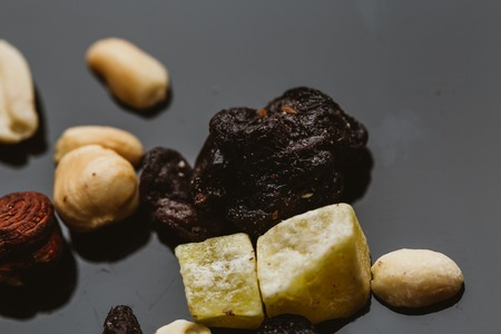 mixture of nuts and dried fruits on a dark background.