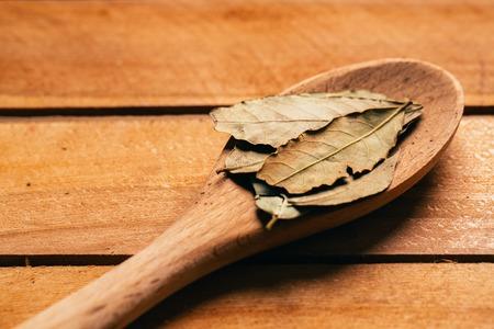 laurierblad in een lichte houten lepel close-up. Stockfoto