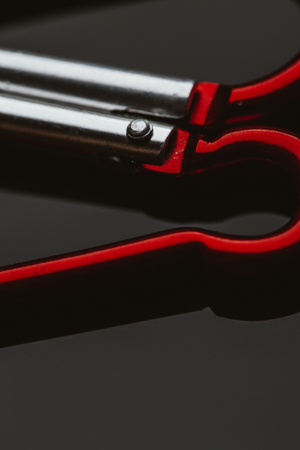 carabiner: several metal carabiner red on a dark background. Stock Photo