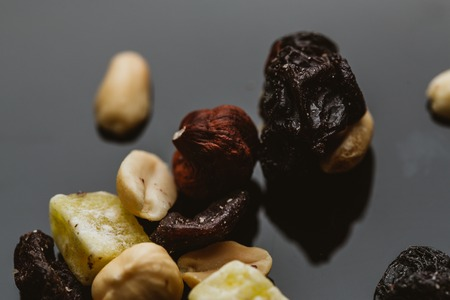 nosh: mixture of nuts and dried fruits on a dark background.