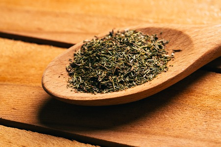 Thyme in a spoon on a light wooden background. Stock Photo