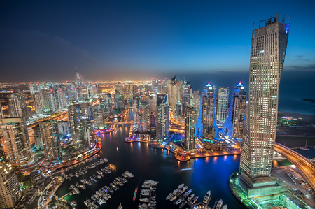 Dubai Marina at Blue hour, Glittering lights and tallest skyscrapers during a clear evening with Blue sky