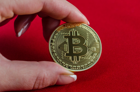 Golden Bitcoins (digital virtual money) in hand on red background.