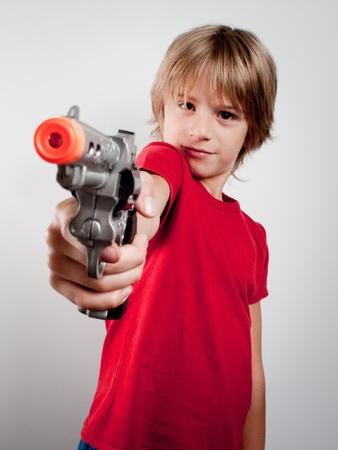 little boy with gun toy