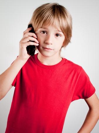 有趣的孩子白衣便攜電話和紅色的襯衫