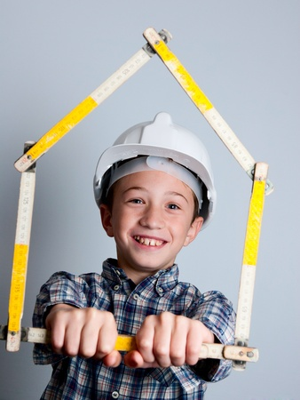 child with white helmet and house photo