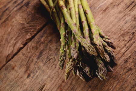 Bunch of fresh asparagus on wooden table photo