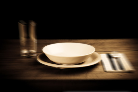 indigent: Empty plate on wooden table blurred style photo