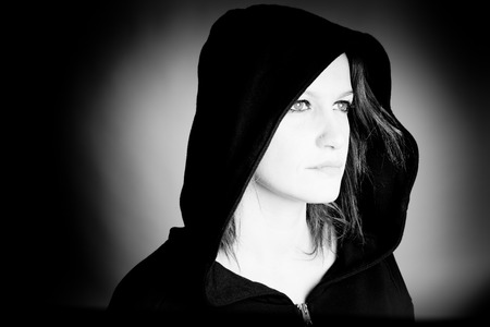 scheming: hooded woman - black and white photo