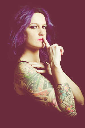 scheming: tattoed dominant woman Stock Photo