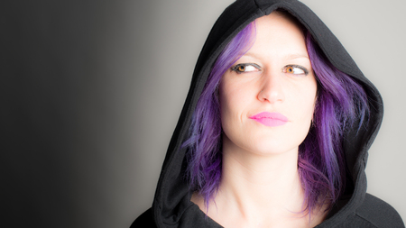 suspected: hooded woman with fuchsia hair and lipstick Stock Photo