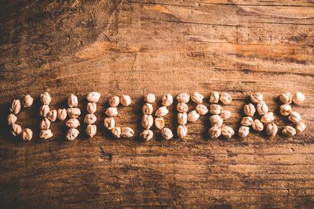 garbanzos: garbanzos escritos en el fondo de madera Foto de archivo
