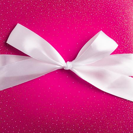 magenta gift box with white ribbon