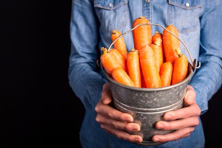 carrots bucket in hands - vegetarian and vegan people