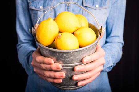 lemons bucket in hands - vegetarian and vegan people