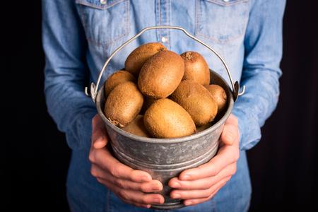 kiwi bucket in hands - vegetarian and vegan people