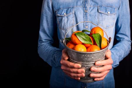 tangerines bucket in hands - vegetarian and vegan people