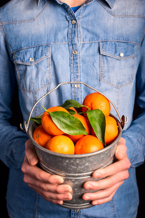 tangerines bucket in hands - vegetarian and vegan people photo