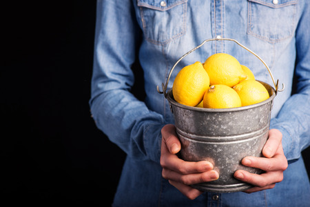 lemons bucket in hands - vegetarian and vegan people photo