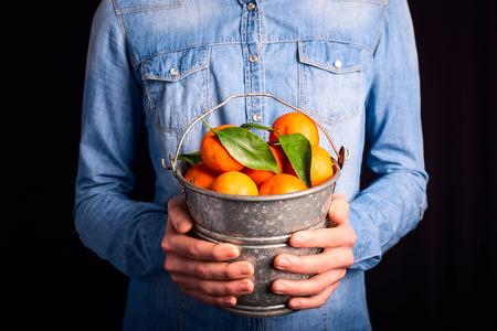 tangerines bucket in hands - vegetarian and vegan people photo