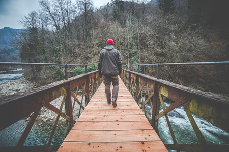 man crosses an iron and wooden footbridge  wood on the river - outdoor activity