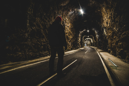 man standing at the entrance of an illuminated tunnel - outdoor activity